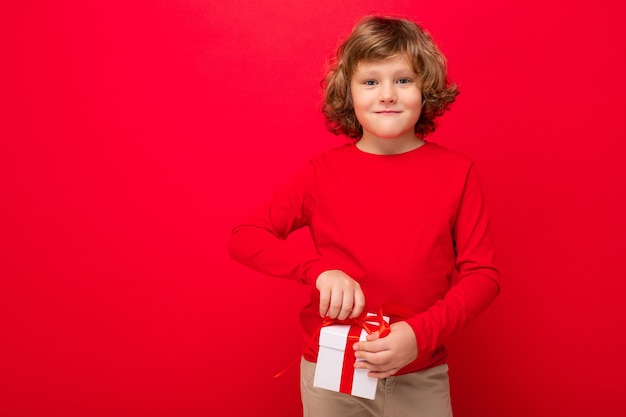 행복 미소 금발 곱슬 남자 아이의 사진 선물 상자를 들고 빨간 스웨터를 입고 빨간색 배경 벽 위에 절연