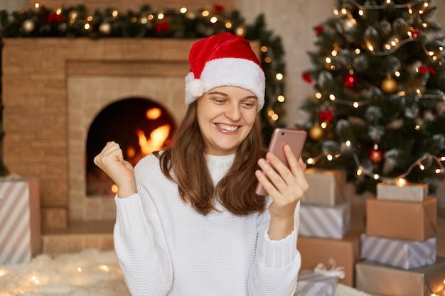 Фотография счастливой улыбающейся девушки читает рождественские новости на смартфоне, поднимает кулаки, сидя в доме
