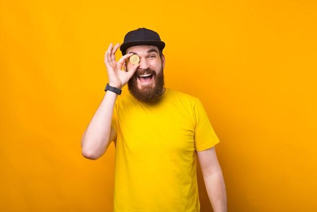 Фотография счастливого улыбающегося человека с бородой, держащего биткойн над глазами
