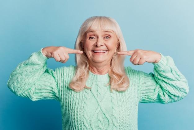 파란색 배경에 고립 된 빛나는 미소 여자 연금 포인트 하얀 치아에 행복의 사진