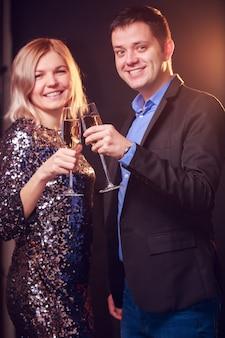 華麗なドレスを着た幸せな女性と黒の背景にシャンパンとワイングラスを持つ男性の写真