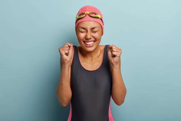 Фотография счастливой женщины в купальном костюме, празднует победу в соревнованиях, сжимает кулаки, простужается в помещении, активно проводит летние каникулы, тренируется в бассейне, использует защитные очки и кепку.