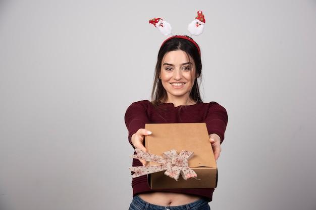 ヘッドバンドを身に着けて、贈り物を提供している幸せな女性の写真。