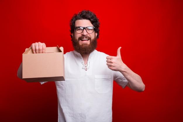 Фото счастливого работника держа коробку для завтрака и показывая большой палец руки вверх