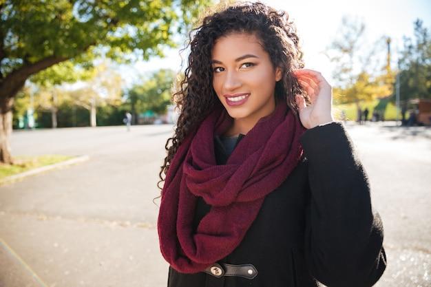 彼女の髪に触れているスカーフを身に着けている幸せな若い暗い肌の巻き毛の女の子の写真脇を見てください。