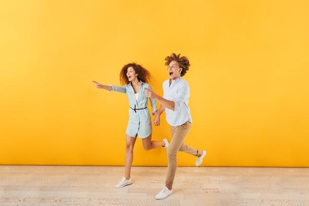 Фотография счастливого молодого мужчины и женщины, бегущих и указывающих пальцами в сторону на copyspace, изолированных на желтом фоне