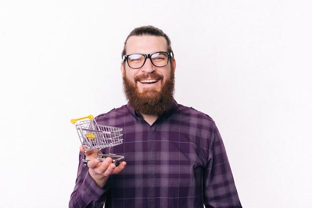 小さなショッピングトロリーを保持している幸せな若い男の写真