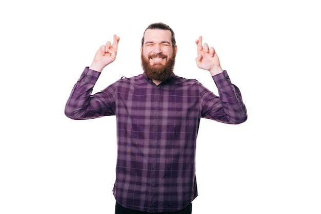 흰 벽에 캐주얼 횡단 손가락에 행복 한 젊은 남자의 사진
