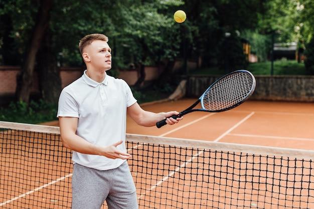 폴로 셔츠를 입은 행복한 청년이 테니스 라켓을 들고 테니스 코트에 서서 웃고 있는 사진.