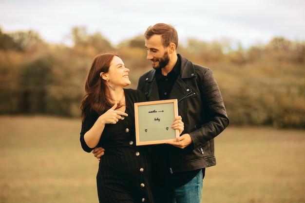 幸せな若い妊娠中のカップルの写真、お互いを見て、名前のプラカードを持っています