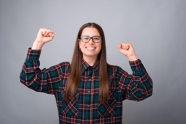 Фото счастливой молодой женщины празднуют победу над белой стеной