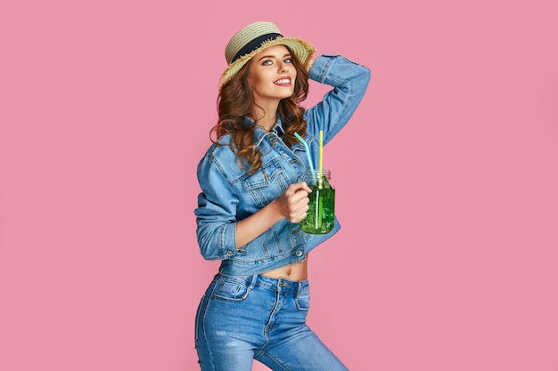 Фотография счастливой молодой женщины в джинсовой одежде и летней соломенной шляпе имеет хорошее настроение, изолированное в пастельно-розовом цветовом пространстве