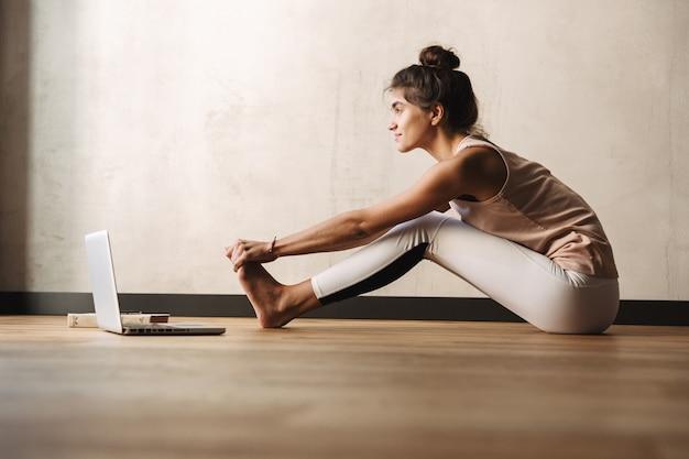Фотография счастливой молодой женщины в спортивной одежде, делающей упражнения и использующей ноутбук, сидя на полу дома