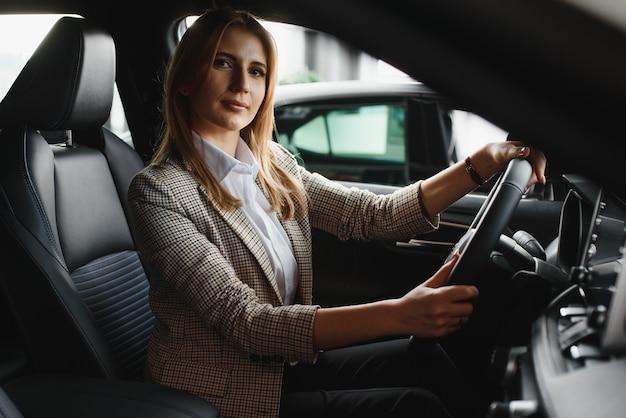 그녀의 새 차 안에 앉아 행복 한 젊은 여자의 사진. 렌터카 개념