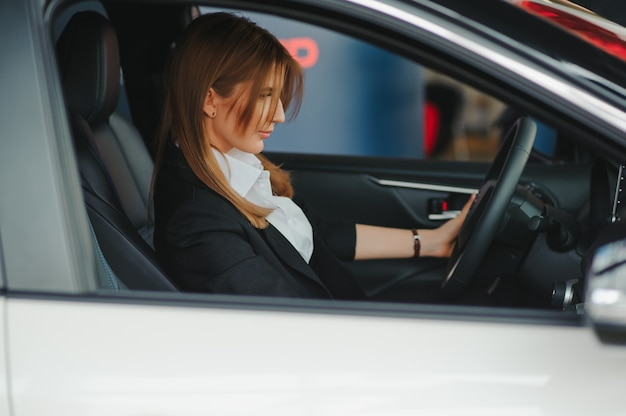 彼女の新しい車の中に座っている幸せな若い女性の写真。レンタカーのコンセプト