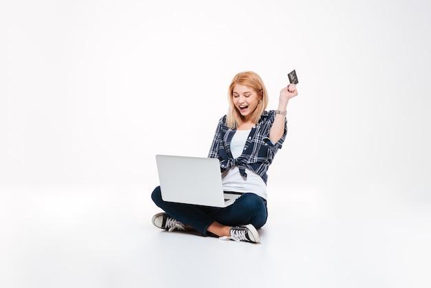 Фото счастливой молодой женщины с помощью портативного компьютера, изолированного на белом фоне, держа дебетовую карту.