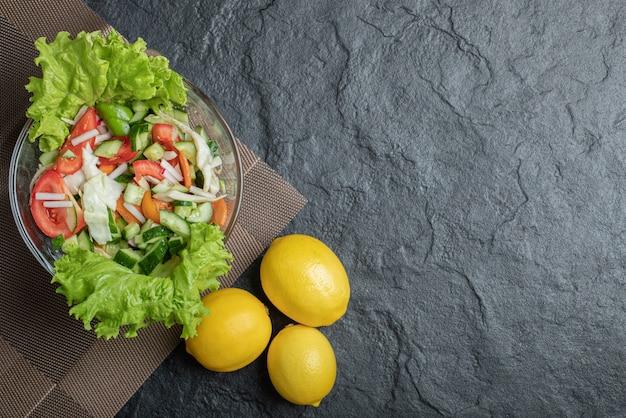 黒の背景に健康的なビーガンサラダの写真。高品質の写真