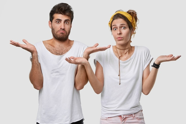 躊躇している彼氏とガールフレンドの写真は不確実に見え、提案を受け取り、疑わしい表情をしており、壁とワントーンで白いtシャツを着ています
