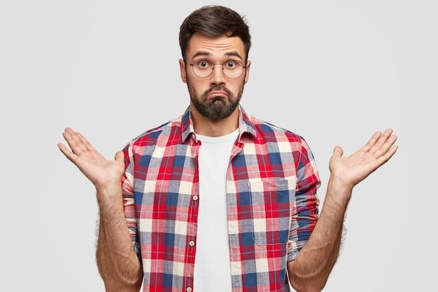 躊躇している無精ひげを生やした男性がためらって手を握りしめ、無知な表情をしていて、何をすべきか疑問に思っている、市松模様のシャツを着て、白い壁に立っている写真。人と混乱の概念