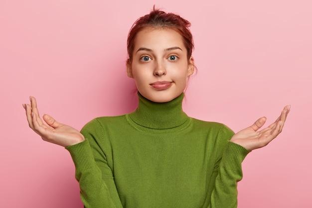 躊躇している若いヨーロッパの女性の写真は、手のひらを広げ、表現が混乱し、決定を下すことができず、緑のタートルネックを身に着け、見た目が気づかず、ピンクの背景にポーズをとっています。