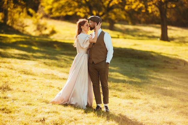 流行に敏感なカップルの写真。自然と日光に囲まれた花嫁に優しくキスする新郎
