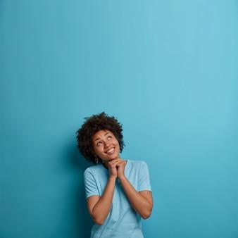 希望に満ちたポジティブな若い女性の写真は、あごの下で手をつないで、上を見て、楽しい割引を見て幸せで、より良いと信じて希望し、カジュアルな青いtシャツを着て、上向きに空きスペースを作ります