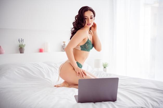 Фотография горячей возбужденной дамы дома удаленная работа онлайн частный чат с ноутбуком раздевается, показывая дразнящие формы, смотреть на экран, тендер, готов показать больше за деньги, носить бикини, простыни, спальня в помещении