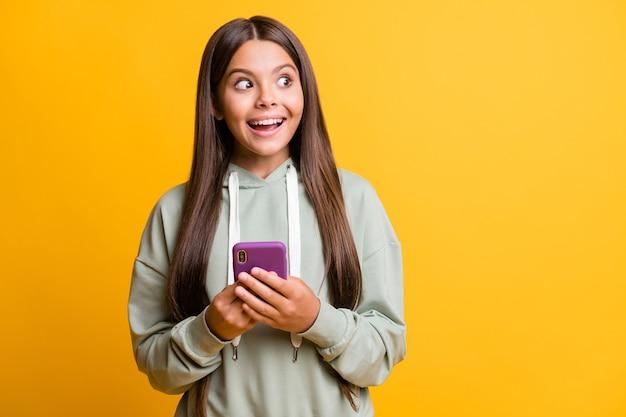 印象的な子供の女の子の写真は、空のスペースを分離された黄色の背景を探している腕の手を現代のデバイスを保持しているカジュアルな緑の服を着ています