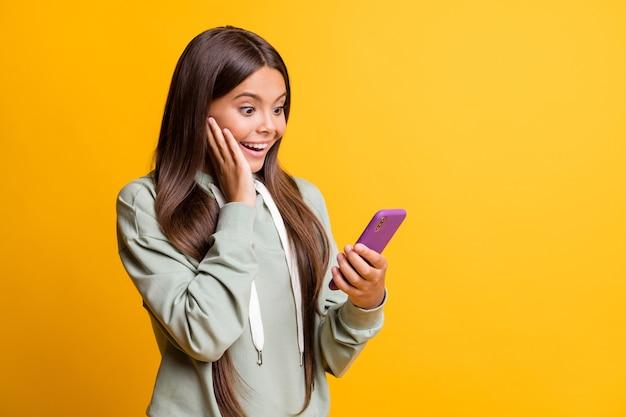 印象的な子供の女の子の写真は、モダンなデバイスの腕の頬を分離した黄色の背景を保持しているカジュアルな緑の服を着ています