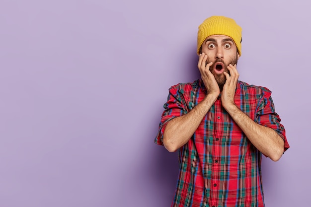 인상적인 젊은 남성의 사진은 멍청한 표정으로 시선을 사로 잡고 뺨에 손을 대고 세련된 옷을 입고 나쁜 소식에 겁에 질려