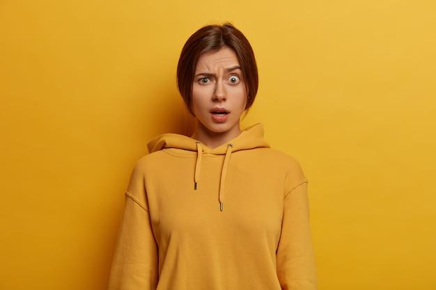 분개 한 젊은 유럽 여성의 사진은 눈썹을 높이고, 예상치 못한 표정을 짓고, 얼굴을 웃으며, 캐주얼 까마귀를 입고, 경이를 표현하고, 노란색 벽에 포즈를 취합니다. 인간의 얼굴 표정 개념