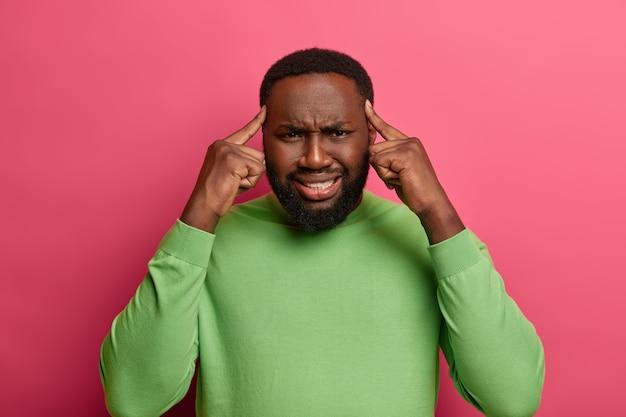 На фото интенсивный бородатый рабочий, страдающий головной болью из-за долгого рабочего дня, держит указательные пальцы на висках, ухмыляется.