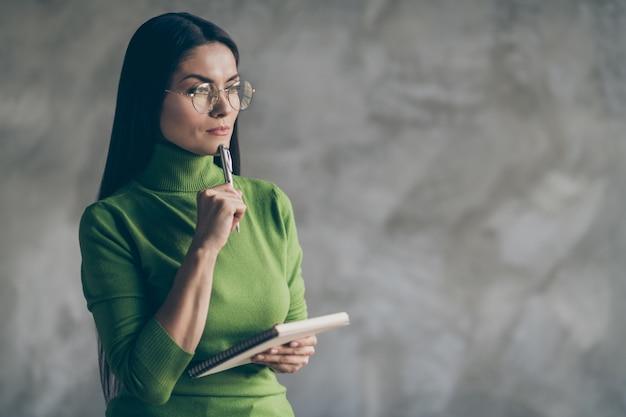 メモ帳孤立した灰色の壁のコンクリート色の背景を保持している彼女の将来の計画について思慮深く考えている興味のある熟考する女性の写真
