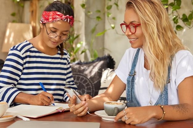 인종 간 여자 친구의 사진은 커피 숍에서 자유 시간을 보냅니다.
