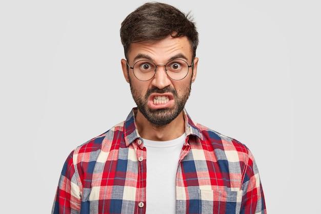イライラした無精ひげを生やした男の写真は、怒って見え、歯を食いしばり、眉を上げ、仕事で多くの仕事に悩まされ、市松模様のシャツを着て、白い壁に立っています。