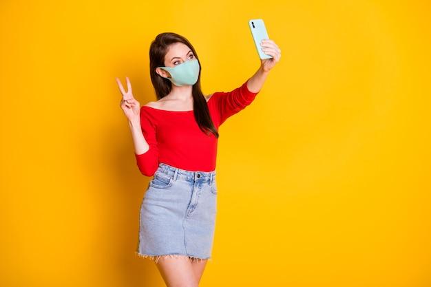 医療マスクの喜びの女の子の写真は、明るい輝きの色の背景の上に分離された赤いトップデニムジーンズの短いミニスカートを身に着けているvサインを取るcovid検疫ブログをお楽しみください