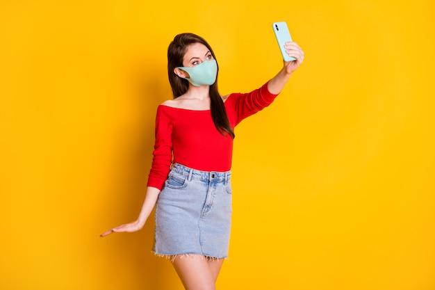 医療マスク使用スマートフォンの喜びの女の子の写真は、明るい輝きの色の背景の上に分離された赤いトップショートミニスカートを自撮りコビッド検疫に着用させます