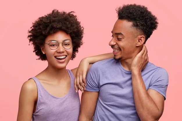 喜びに満ちた浅黒い肌の女性と男性の仲間の写真は、一緒に喜びを持ち、カジュアルな服を着て、前向きに笑い、ピンクの壁に立ち向かいます。幸せなアフリカ系アメリカ人の女性は男の肩に寄りかかる