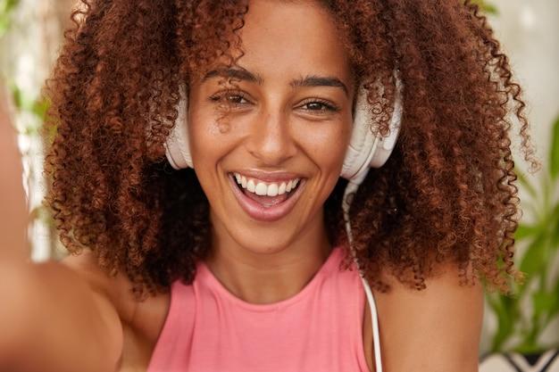 즐거운 어두운 피부 소녀의 사진은 현대 스테레오 헤드폰으로 음악을 듣습니다.