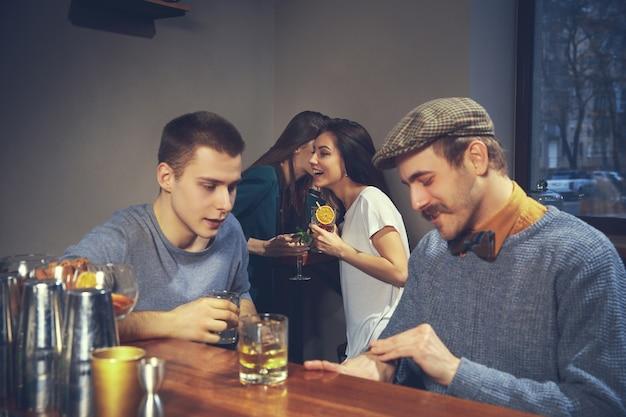 Фотография веселых друзей в баре или пабе, общающихся друг с другом