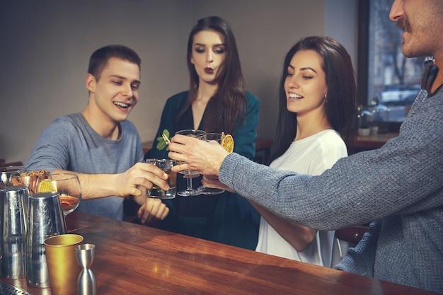 バーやパブでコミュニケーションをとっている楽しい友達の写真
