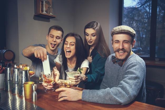 바 또는 술집에서 서로 의사 소통하는 즐거운 친구들의 사진