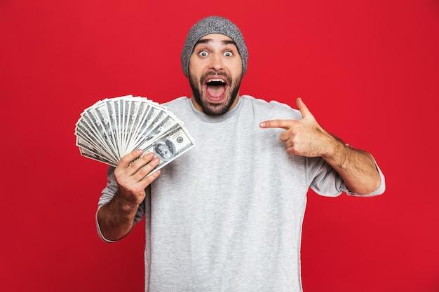 Фотография радостного парня 30-х годов в повседневной одежде, радующегося и держащего наличные деньги изолированными
