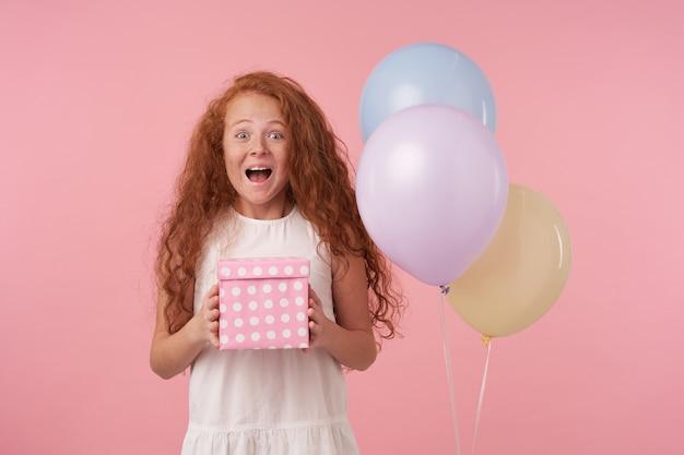 생일 선물에 대해 흥분되는 선물 포장 상자를 들고 분홍색 배경 위에 포즈를 취하는 우아한 흰색 드레스를 입고 붉은 곱슬 머리를 가진 즐거운 어린 소녀의 사진은 진정한 긍정적 인 감정을 표현합니다.