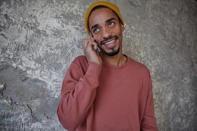 매력적인 미소로 옆으로보고 자신의 휴대 전화로 전화를하는 동안 콘크리트 벽 위에 포즈를 취하는 캐주얼 옷을 입은 수염을 가진 즐거운 사랑스러운 어두운 피부 남자의 사진