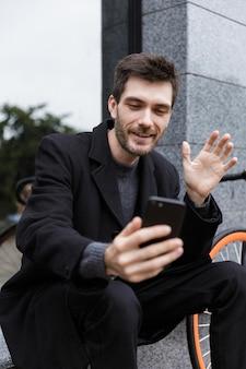자전거와 함께 야외에 앉아있는 동안 휴대 전화에 셀카를 복용하는 즐거운 남자 20 대의 사진