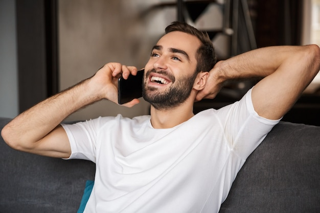 Фотография радостного мужчины 30-х годов в повседневной футболке, говорящего по смартфону, сидя на диване в гостиной