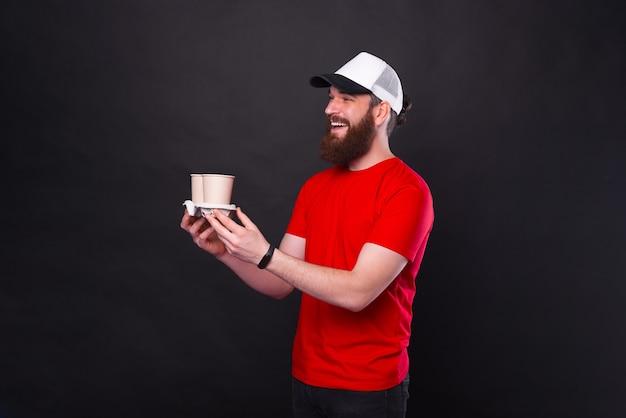 검은 배경 위에 갈 사람에게 두 개의 커피 컵을주는 수염을 가진 즐거운 남자의 사진