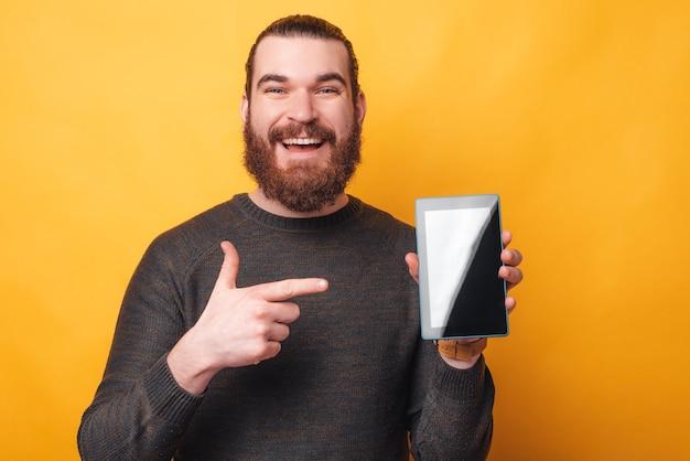 노란색 벽 위에 태블릿을 가리키는 수염을 가진 즐거운 남자의 사진