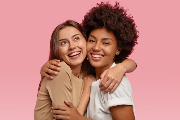 На фото две радостные женщины обнимаются и позитивно улыбаются, имеют мечтательные выражения лица, демонстрируют искренние чувства.